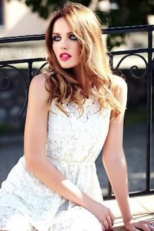 Het portret van de aantrekkingskrachtschoonheid van mooi sensueel kaukasisch jong vrouwenmodel met avondmake-up in het witte de zomerkleding stellen op de straatachtergrond