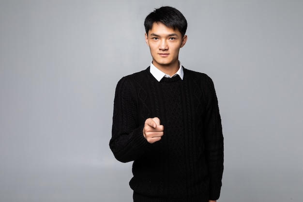 Het portret van de aziatische mens richt vinger op u over geïsoleerde witte muur