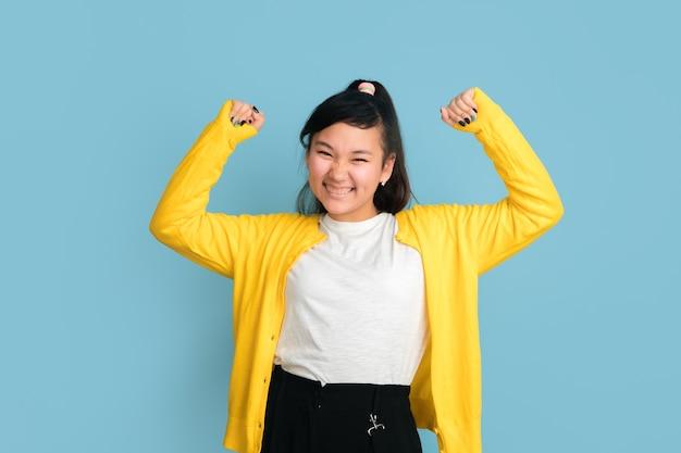 Het portret van de aziatische tiener dat op blauwe studioachtergrond wordt geïsoleerd. mooi vrouwelijk donkerbruin model met lang haar. concept van menselijke emoties, gezichtsuitdrukking, verkoop, advertentie. gelukkig winnen, weddenschap concept.