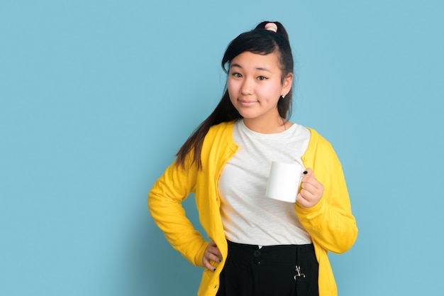 Het portret van de aziatische tiener dat op blauwe studioachtergrond wordt geïsoleerd. mooi vrouwelijk donkerbruin model met lang haar. concept van menselijke emoties, gezichtsuitdrukking, verkoop, advertentie. koffie of thee drinken.