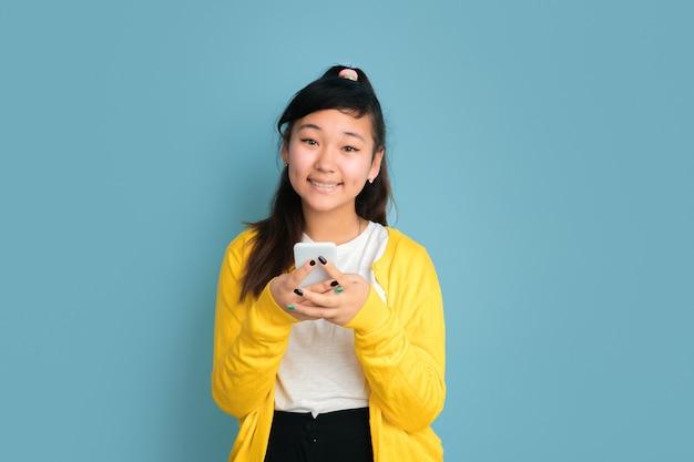 Het portret van de aziatische tiener dat op blauwe studioachtergrond wordt geïsoleerd. mooi vrouwelijk donkerbruin model met lang haar. concept van menselijke emoties, gezichtsuitdrukking, verkoop, advertentie. met behulp van de telefoon, glimlachend.