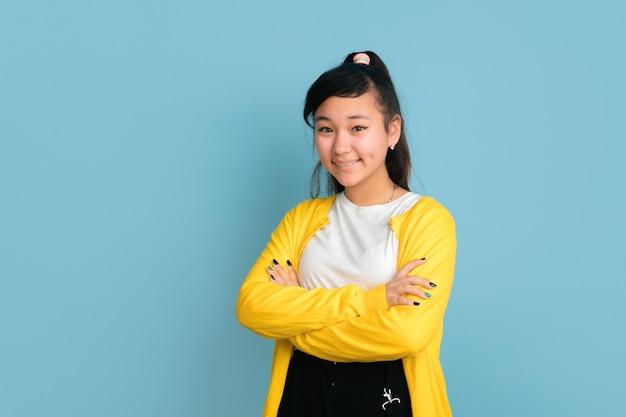Het portret van de aziatische tiener dat op blauwe studioachtergrond wordt geïsoleerd. mooi vrouwelijk donkerbruin model met lang haar. concept van menselijke emoties, gezichtsuitdrukking, verkoop, advertentie. poseren met gekruiste handen.