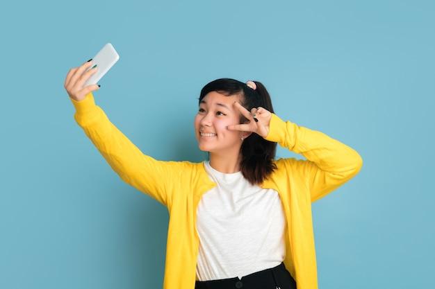 Het portret van de aziatische tiener dat op blauwe studioachtergrond wordt geïsoleerd. mooi vrouwelijk donkerbruin model met lang haar. concept van menselijke emoties, gezichtsuitdrukking, verkoop, advertentie. selfie of vlog maken.