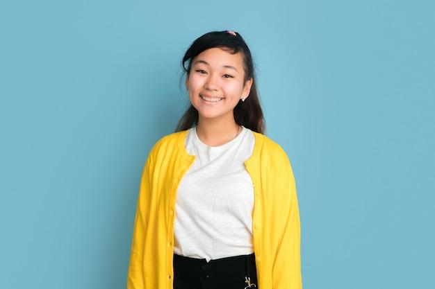 Het portret van de aziatische tiener dat op blauwe studioachtergrond wordt geïsoleerd. mooi vrouwelijk donkerbruin model met lang haar in informele stijl. concept van menselijke emoties, gezichtsuitdrukking, verkoop, advertentie. lachend schattig.