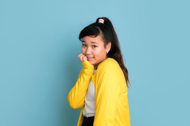 Het portret van de aziatische tiener dat op blauwe studioachtergrond wordt geïsoleerd. mooi vrouwelijk donkerbruin model met lang haar in informele stijl. concept van menselijke emoties, gezichtsuitdrukking, verkoop, advertentie. leuk poseren.