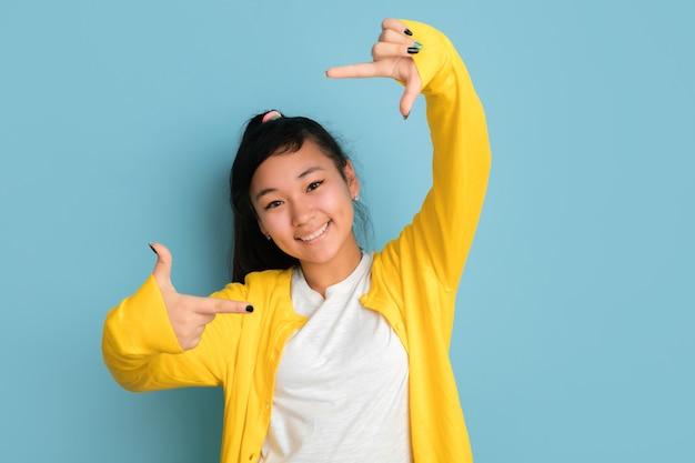 Het portret van de aziatische tiener dat op blauwe studioachtergrond wordt geïsoleerd
