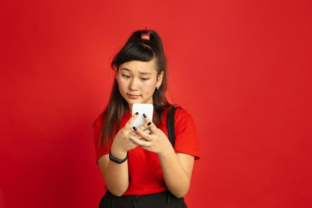 Het portret van de aziatische tiener dat op rode ruimte wordt geïsoleerd