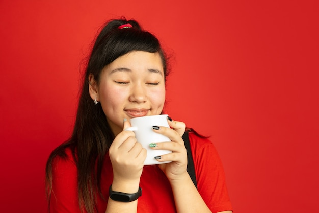 Het portret van de aziatische tiener dat op rode studio wordt geïsoleerd