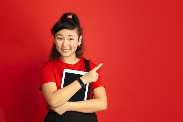 Het portret van de aziatische tiener dat op rode studioachtergrond wordt geïsoleerd. mooi vrouwelijk donkerbruin model in informele stijl. concept van menselijke emoties, gezichtsuitdrukking, verkoop, advertentie. wijzend met tablet, glimlachend.