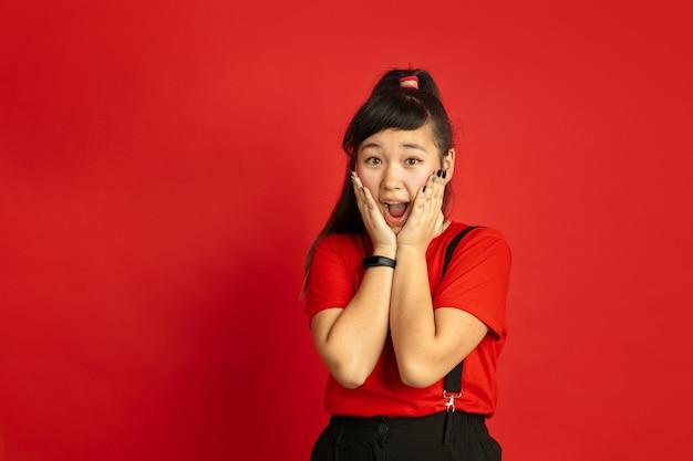 Het portret van de aziatische tiener dat op rode studioachtergrond wordt geïsoleerd. mooi vrouwelijk donkerbruin model met lang haar in casual. concept van menselijke emoties, gezichtsuitdrukking, verkoop, advertentie. verbaasd, geschokt.