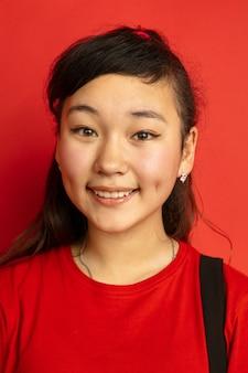 Het portret van de aziatische tiener dat op rode studioachtergrond wordt geïsoleerd. mooi vrouwelijk donkerbruin model met lang haar in informele stijl. concept van menselijke emoties, gezichtsuitdrukking, verkoop, advertentie. lachend schattig.