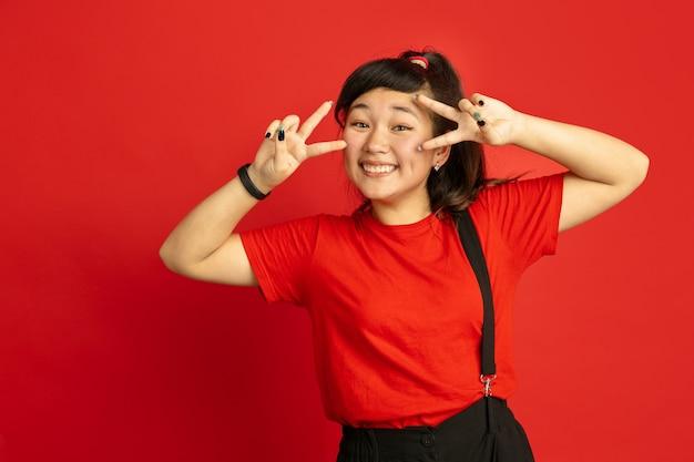 Het portret van de aziatische tiener dat op rode studioachtergrond wordt geïsoleerd. mooi vrouwelijk donkerbruin model met lang haar in informele stijl. concept van menselijke emoties, gezichtsuitdrukking, verkoop, advertentie. leuk poseren.