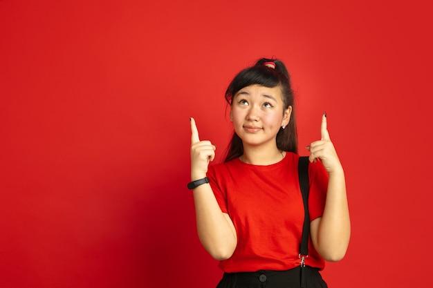 Het portret van de aziatische tiener dat op rode studioachtergrond wordt geïsoleerd. mooi vrouwelijk donkerbruin model met lang haar in informele stijl. concept van menselijke emoties, gezichtsuitdrukking, verkoop, advertentie. naar boven stekend.
