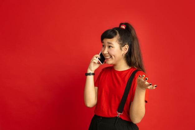 Het portret van de aziatische tiener dat op rode studioachtergrond wordt geïsoleerd. mooi vrouwelijk donkerbruin model met lang haar in informele stijl. concept van menselijke emoties, gezichtsuitdrukking, verkoop, advertentie. praten aan de telefoon.