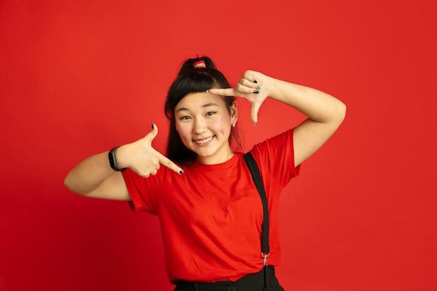 Het portret van de aziatische tiener dat op rode studioachtergrond wordt geïsoleerd. mooi vrouwelijk donkerbruin model met lang haar in informele stijl. concept van menselijke emoties, gezichtsuitdrukking, verkoop, advertentie. selfie inlijsten.