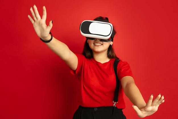 Het portret van de aziatische tiener dat op rode studioachtergrond wordt geïsoleerd. mooi vrouwelijk donkerbruin model met lang haar in informele stijl. concept van menselijke emoties, gezichtsuitdrukking, verkoop, advertentie. speelt vr-headset.