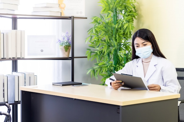 Het portret van de aziatische vrouwelijke arts draagt beschermend gezichtsmasker zit in haar kantoorruimte in de ziekenhuiskliniek en leest op gedulddossier alvorens geduld te controleren. nieuw normaal gezondheidszorgconcept.