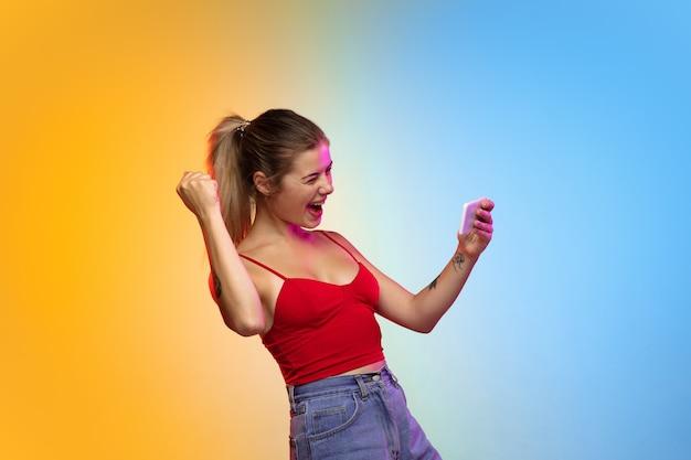 Het portret van de blanke jonge vrouw op de achtergrond van de gradiëntstudio in neon