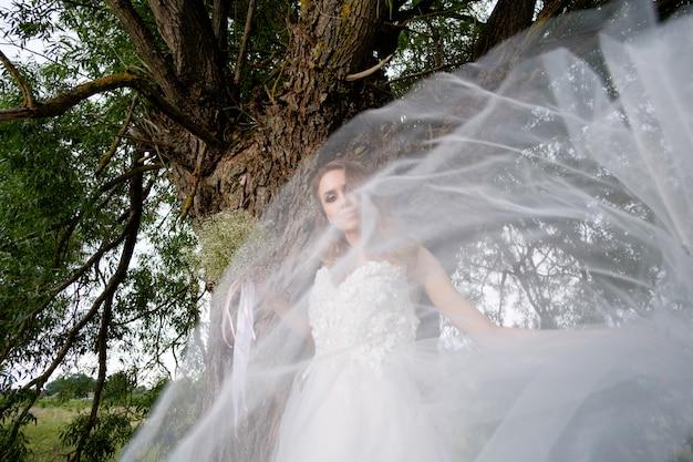 Het portret van de bruid door sluier in openlucht