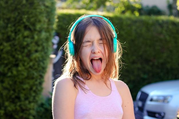 Het portret van de close-up van grappig preteen meisje met draadloze hoofdtelefoons op hoofd