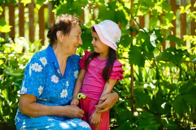 Het portret van de close-upzomer van gelukkige grootmoeder met kleindochter