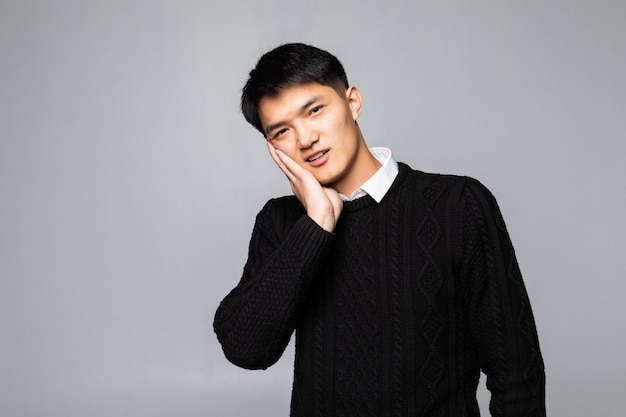 Het portret van de dikke aziatische mens gebruikt zijn hand raakt zijn wang, voelend pijnlijk van kiespijn. mondgezondheid concept.