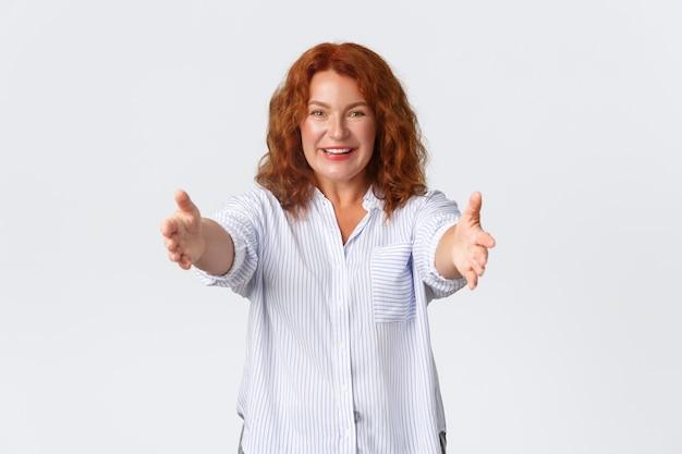 Het portret van de gelukkige en mooie roodharige vrouw van middelbare leeftijd strekt zijn handen uit, reikt armen voor omhelzing, moeder wil iemand knuffelen of omhelzen. vrouw ontvangt een geschenk en neemt het, witte achtergrond.