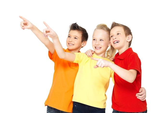 Het portret van de gelukkige kinderen wijst met de vinger op iets weg - geïsoleerd op wit