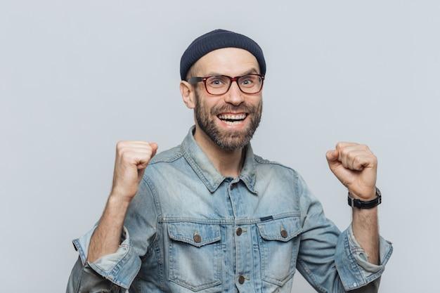Het portret van de gelukkige succesvolle mens verheugt zich zijn triomf, klemt tanden, heeft dolblij op uitdrukking