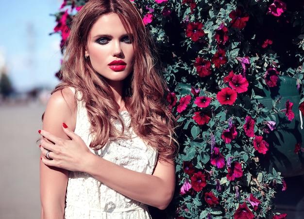 Het portret van de glamourschoonheid van mooi sensueel kaukasisch jong vrouwenmodel met avondmake-up in het witte de zomerkleding stellen op de straatachtergrond dichtbij bloemenachtergrond