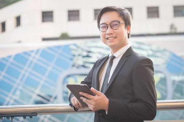 Het portret van de glimlachende bedrijfsmens kijkt zeker gebruikend computertablet
