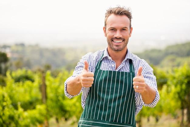 Het portret van de glimlachende jonge mens die duimen tonen ondertekent omhoog