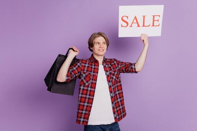 Het portret van de grappige kerel houdt de koopjesbanner van het winkelcentrum vast, kijk omhoog op violette achtergrond