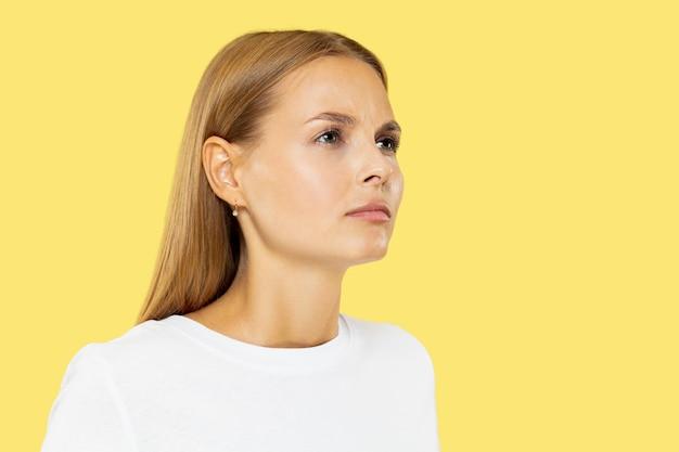 Het portret van de halve lengte van de kaukasische jonge vrouw op gele studio
