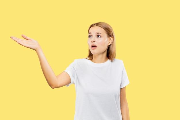 Het portret van de halve lengte van de kaukasische jonge vrouw op gele studioachtergrond. mooi vrouwelijk model in wit overhemd. concept van menselijke emoties, gezichtsuitdrukking. een lege ruimte tonen of uitnodigend.