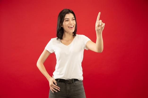 Het portret van de halve lengte van de kaukasische jonge vrouw op rode studioachtergrond. mooi vrouwelijk model in wit overhemd. concept van menselijke emoties, gezichtsuitdrukking. lege zoekbalk aanraken, copyspace.