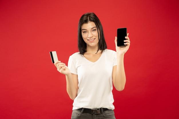 Het portret van de halve lengte van de kaukasische jonge vrouw op rode studioachtergrond. mooi vrouwelijk model in wit overhemd. concept van menselijke emoties, gezichtsuitdrukking, verkoop. online betalingsrekening of aankopen.