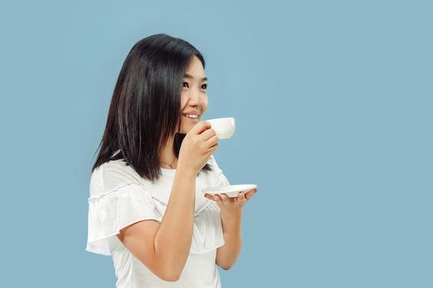 Het portret van de halve lengte van de koreaanse jonge vrouw op blauwe studio