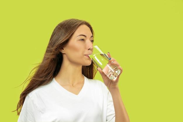 Het portret van de halve lengte van de mooie jonge vrouw geïsoleerd. vrouwelijk model ziet er gelukkig uit en drinkt water. gelaatsuitdrukking, concept van menselijke emoties, schoonheid en gezondheidszorg.