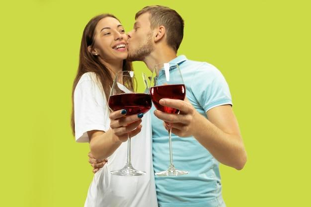 Het portret van de halve lengte van het mooie jonge paar geïsoleerd. vrouw en man met glazen rode wijn. gelaatsuitdrukking, zomer, weekendconcept. trendy kleuren.