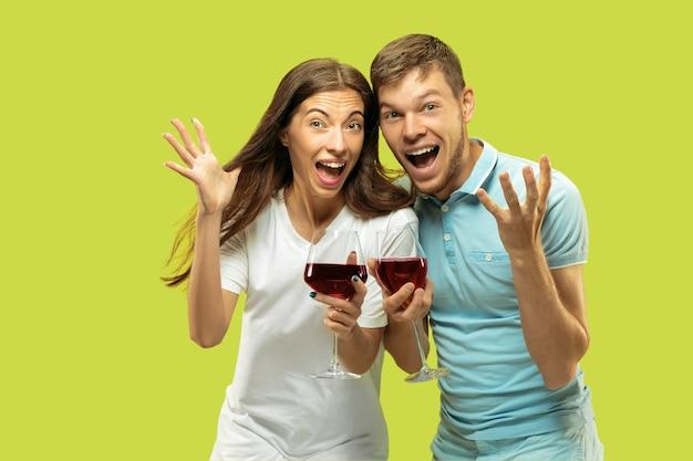 Het portret van de halve lengte van het mooie jonge paar geïsoleerd. vrouw en man met glazen rode wijn selfie maken. gelaatsuitdrukking, zomer, weekendconcept. trendy kleuren.