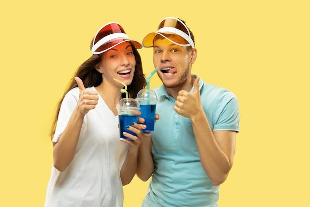 Het portret van de halve lengte van het mooie jonge paar geïsoleerd. vrouw en man permanent met drankjes in kleurrijke hoofdletters. gelaatsuitdrukking, zomer, weekendconcept. trendy kleuren.