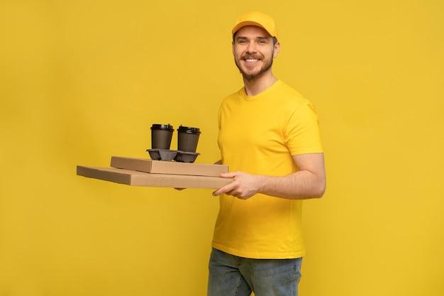 Het portret van de jonge bezorger in geel uniform met pizzadozen en haalt koffie weg die over gele muur wordt geïsoleerd