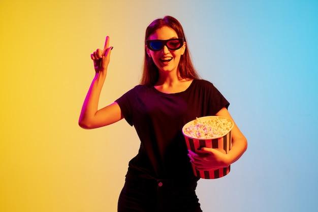 Het portret van de jonge blanke vrouw op de achtergrond van de gradiëntblauwgele studio in neonlicht