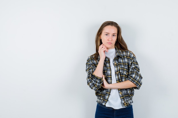 Het portret van de jonge dame die zich in het denken bevindt stelt in t-shirt, jasje, spijkerbroek en op zoek doordachte vooraanzicht