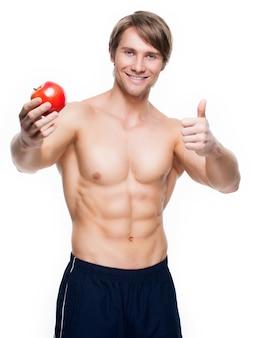 Het portret van de jonge gelukkige appel van de bodybuilderholding in zijn hand en toont duimen omhoog teken - dat op witte muur wordt geïsoleerd.
