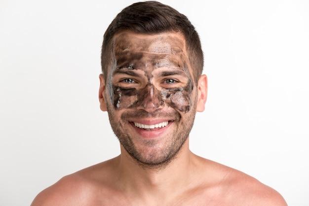 Het portret van de jonge glimlachende mens paste zwart masker op gezicht toe en bekijkend camera