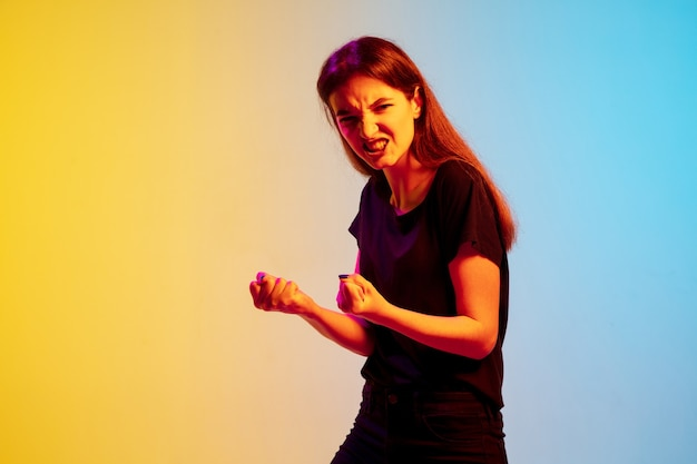 Het portret van de jonge kaukasische vrouw op de achtergrond van de gradiëntblauw-gele studio in neonlicht