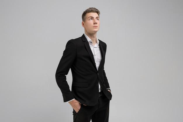 Het portret van de jonge mens met dient zakken in zwart die kostuum in op witte achtergrond wordt geïsoleerd
