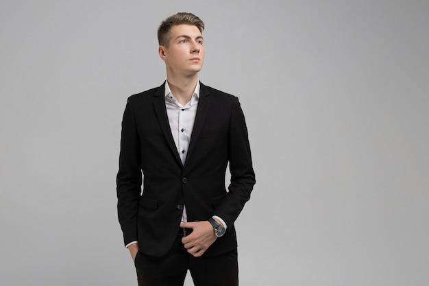 Het portret van de jonge mens met dient zakken in zwart geïsoleerd kostuum in